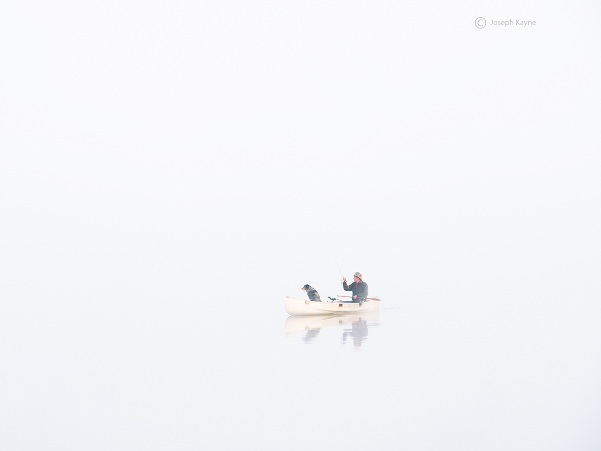 A Lone Fisherman & His Dog Canoeing In A Vermont Pond
